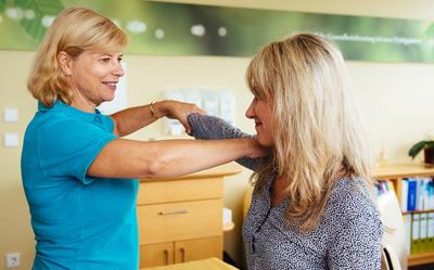 Prävention: Dr. Niemer macht Übungen mit einer Patientin in der Praxis in Künzelsau